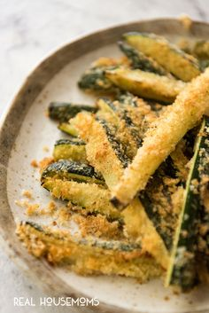 Close up of Super Easy Parmesan Crust Zucchini piled up on a plate.