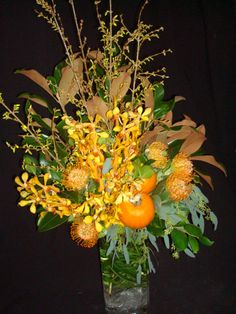 An arrangement featuring yellow mokara orchids, yellow forsythia, magnolia branches and pumpkins.  To view our entire selection please visit us at www.starflor.com #flowers #events #eventdecor