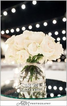 Love the clean and simple centerpiece of white roses on a mirror with market lighting overhead in an outdoor reception or cocktail hour. Great picture!
