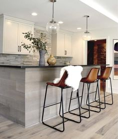 Three CB2 Roadhouse Leather Barstools sit on light gray oak stain wood floors in front of a gray oak island accented with a black quartz countertop illuminated by clear glass globe pendants.