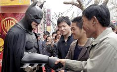 an actor clad in a Batman costume greets local spectators after the grand opening ceremony of the Warner Bros. Studio Store in Shanghai, China May, 2013