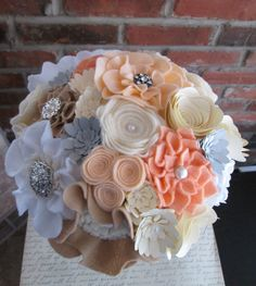 This unique felt and paper bouquet features stunning individually crafted flowers with sparkly brooch and pearl detailing. This elegant bouquet would be a lovely addition to your wedding and can be saved forever as a memento of your special day without wilting! This custom bouquet is sold, but I would love to make your own custom creation. This bouquet spans approximately 9 inches and each flower is hand cut and crafted, so there are no two flowers exactly alike. The colors featured here are…