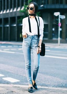A white top is worn with a skinny scarf, high-waisted jeans, round sunglasses, and loafers