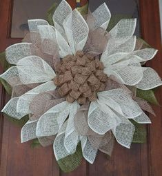 This country sunflower is made with antique white and natural poly burlap for the petals, and olive green poly burlap for the leaves. The center is created with traditional burlap. It is approximately 26 in diameter, and can be safe for outdoor display. Please remember that though