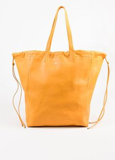 "A bright and fun tote by Celine that will become your ultimate accessory. Smooth leather in a ""Daffodil"" yellow hue. The ""Large Coulisse"" style features a drawstring top closure and soft sides. Two to"