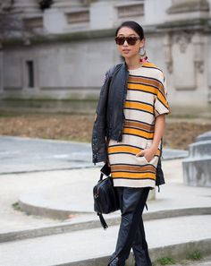 Margaret Zhang wears oversize earrings, sunglasses, striped tunic dress and leather pants.