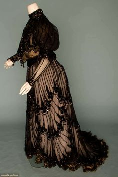 "BLACK LACE TEA GOWN, c. 1905  2-piece, velvet dot appliques, chenille embroidery & black sequin trim on cross-hatch patterned net, B 36"", W 26"", Skirt L 40""-50"","
