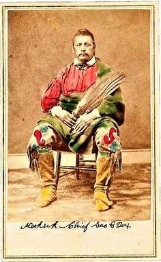 Carte de Visite: Chief Keokuk, Sac -Fox, by A. W. Barker - Ottawa, Kansas c. 1860s. A seated Keokuk holds a ceremonial wing, and wears beaded pants and hi-top boots with a blanket about his shoulder and lap. Hand-colored.