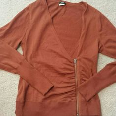 J crew zip up sweater. The color of the cardigan/swaeter is a rust orange/brown. It has a deep V,and zips at the side.  It is a light fabric/material so appropriate for spring or fall. J. Crew Sweaters Cardigans