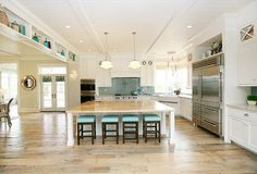 White Kitchen Ideas. Open kitchen design with beadboard ceiling, farmhouse sink, blue glass tiles backsplash, schoolhouse pendants, white custom cabinets, white countertops, pot filler, white kitchen island, butcher block countertops, espresso stained counter stools with blue vinyl tufted cushion.  White Kitchen. #WhiteKitchen