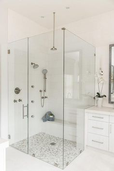 White and gray river rock stone shower floor tiles add a dimensional and natural looking finish to a seamless glass walk-in shower with a marble bench and multiple shower heads.