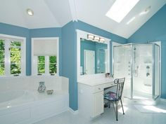 This white and blue bathroom is incredibly spacious, with a soaking tub in front of the bay windows and an enormous shower enclosure. We just love the colorful floral pattern of the chair beneath the skylight. What do you think of this bright bathroom? Source: http://www.zillow.com/digs/Home-Stratosphere-boards/Luxury-Bathrooms/