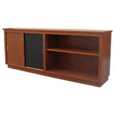 This mid-century modern storage unit features an open shelf on one side and a cabinet with sliding doors on the other. The Danish case piece is made of teak with one of the cabinet doors lacquered black; the fittings are brass.