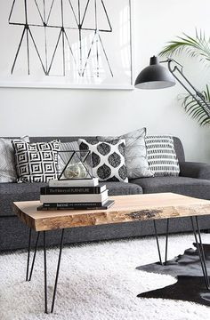 The straight lines on the table, straight lines in the picture, on the table decoration, the pillows … Plant in a corner of the room (we can see only the leaves) enriches this space and helps it does not look cold.
