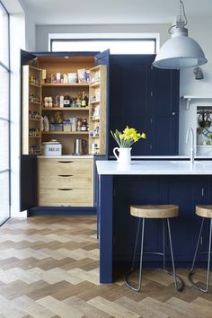 Navy cabinets paired with parquet floors. Blakes London