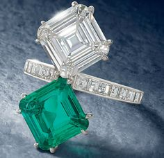 EMERALD AND DIAMOND RING, BY CARTIER  Designed as a square step-cut diamond weighing approximately 4.08 carats confronting a similarly-cut emerald weighing approximately 3.59 carats, set diagonally on the diamond-set tapering band, French marks for platinum, maker's case, one diamond deficient  Signed Cartier and no.709619 52 .  Image: Christies