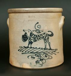 "Sold $750 Rare Six-Gallon Stoneware Crock with Cobalt Decoration of a Dog with Basket, Stamped ""HART'S/ FULTON,"" New York State origin, circa 1880, cylindrical crock with applied lug handles, decorated with a large slip-trailed design of a dog carrying a basket in its mouth. Folky striped and spotted detail to dog's body. Stylized stripe and looping line detail t"