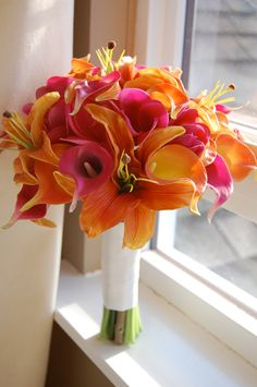 Orange and fuchsia plumeria, tiger lilies and calla lilies bridal bouquet.