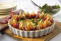 Spinach pie topped with salami, cape gooseberries and pomegranat - Oatly