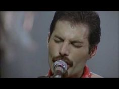 "Freddie Mercury and Queen live ""We Are the Champions"".  [Sasha Baron Cohen is going to play him in a biopic.]"