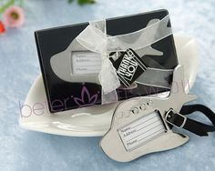 """Destination Love"" Chrome Luggage Tag Fly the romantic skies! Travel buffs and frequent fliers alike will adore the utility of this special little favor. What a great way to thank your guests for traveling to your event. Brides will love the touch of sophisticated whimsy these placecard holders add to any reception table. Each plane-shaped tag is crafted of substantial chrome and is dotted with charming heart-shaped ""windows"". Attached is a black adjustable leather strap."