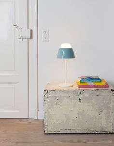 A blue painted steel table lamp with a mouthblown glass tip.