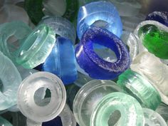 Think: could one set these into a concrete slab to make light permeable shower wall? 😆 Recycled Glass Bottle Tops Slumped into Donuts and Sea Glass Recycled Glass Bottles, Glass Bottle Crafts, Sea Glass Crafts, Bottle Art, Fused Glass Jewelry, Fused Glass Art, Mosaic Glass, Slumped Glass, Concrete Slab