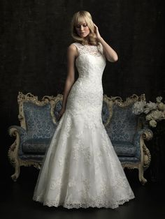 This slim, fitted gown in all-over lace features a beautiful, raised neckline with contoured straps that continue to a keyhole back. A chapel length train and covered buttons complete this style.