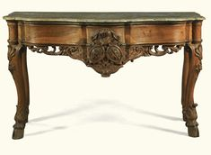 A Rococo carved oak console table with marble top South Germany, circa 1750 the moulded shaped marble top above a conforming plain frieze above a trellis ground pierced and carved armorial apron, on shell carved cabriole legs on hoof feet Sotheby's