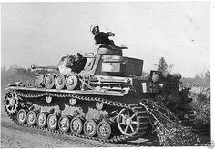 """A late variant Panzer 4 with the Panzergrenadier-Division """"Großdeutschland"""" using tree branches at the rear of the tank attempting to dampen the dust created by traveling to a minimum so as not to give their position away while the commander looks to the sky for any Allied fighter bomber threats."""