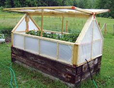 A raised garden bed with a greenhouse