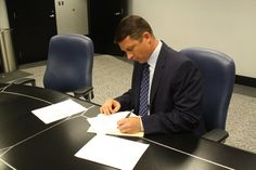 Carolina Panthers K John Kasay signing his one-day contract in order to retire a member of the Carolina Panthers.