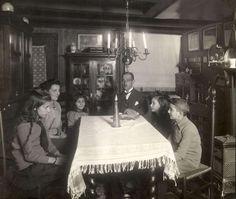 Joodse godsdienst. Gezin rond de tafel ter viering van het Israëlische Chanoeka/Inwijdingsfeest. Dit feest duurt 8 dagen. Foto 1922.