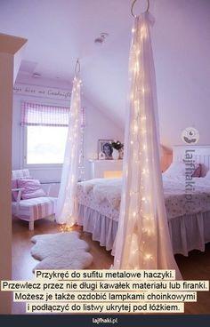 Jak urządzić pokój dla nastolatki - Przykręć do sufitu metalowe haczyki. Przewlecz przez nie długi kawałek materiału lub firanki. Możesz je także ozdobić lampkami choinkowymi i podłączyć do listwy ukrytej pod łóżkiem.