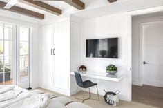 Minimalistic white bedroom space featuring a built in wardrobe cabinet and a floating glass top desk.