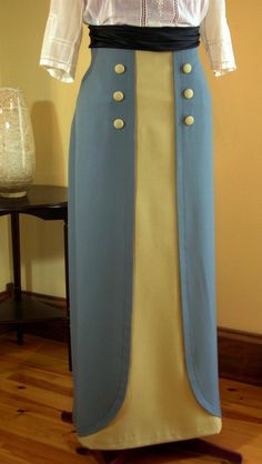 """The 1912 """"tulip skirt"""" (sewing pattern #1912-A-010), shown in steel blue and soft gold wool gabardine,worn with a black satin sash and antique lingerie blouse,"""