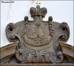 This interesting stone alliance coat of arms of two Bohemian noble families - Kinský & Harrach you can find above entrance doors of early-Baroque church of St. Isidor (kostel Sv. Izidora) located near village Budenice-Jerpice in Central Bohemia.