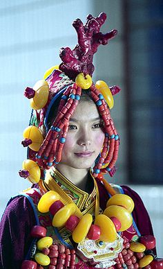 Well this girl has it all. Amber red coral and turquoise.  (Not to mention a peaceful confident countenance.) Khampa Tibetans Headdresses part 1