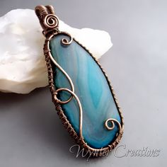 Simple, elegant wire work accents the bright teal of an dyed agate slice for a pendant that really pops!  The bezel frame for the pendant was woven by hand from pure copper wire and embellished with hand-formed scroll work that holds the stone securely in place. The entire piece was antiqued and buffed to a rich glow.
