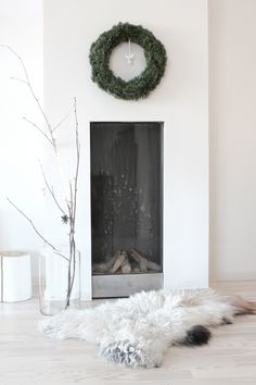 simple wreath and tree and a large fur surround a minimal fireplace--image via Sonya Teems