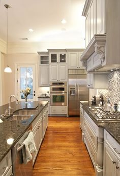 grey kitchen cabinets, black granite counter tops, wood floors