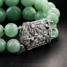 Gently graduating in size from 8.5 to just over 12 millimeters, from the ends to the center, two strands of 28 bright apple green natural Burma jade beads, join to make a stunning wrist bauble. Equally stunning, however, is the spectacular platinum and diamond Art Deco centerpiece, circa 1930, that does double duty as the clasp. A rare beauty to wear alone or to compliment a jade bead necklace. The clasp measures 1 inch by 11/16 inch. The bracelet measures 7 inches.