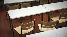 Tyhjiä pulpetteja tuoleineen koulun luokassa.