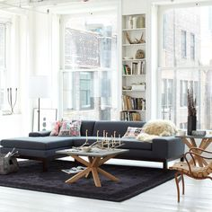living room: mod navy sofa, bright whites, & furniture w/ wood accents