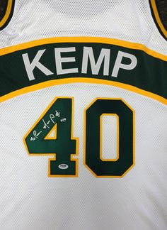 This is a white Seattle Sonics jersey that has been hand signed by Shawn Kemp. This is a custom jersey with no name brand. The approximate size is XL. It has nice sewn in name and numbers. This jersey