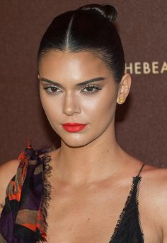 For a fresh take on a slicked-back bun, Kendall rocks a razor-sharp centre-parting. For the first step, use wet-look gel to smooth it down and tie into a pony. Then twist the hair, wind it up into a bun shape and secure with an elastic. As chic as it is quick