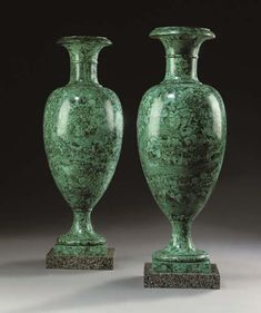 A PAIR OF RUSSIAN MALACHITE VASES  EARLY 19TH CENTURY  Each with an ovoid body with a waisted neck, on a spreading circular shaft, on a square porphyry plinth  28½ in. (72,5 cm.) high; 10 in. (25,5 cm.) wide; 10 in. (25,5 cm.) deep (2)