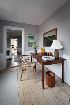 Love the combination of grey walls, white panels, pale wood floorboards and soft grey rug. Great chair too!