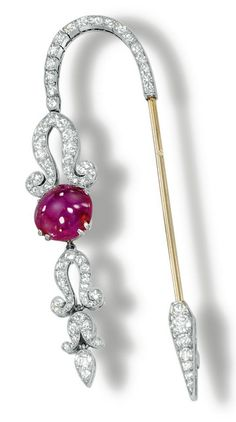 Ruby and diamond jabot pin, Janesich, 1920s. Designed as single- and circular-cut diamond cascade motif set with a cabochon ruby, mounted in platinum, signed Janesich and numbered, French assay and maker's marks.