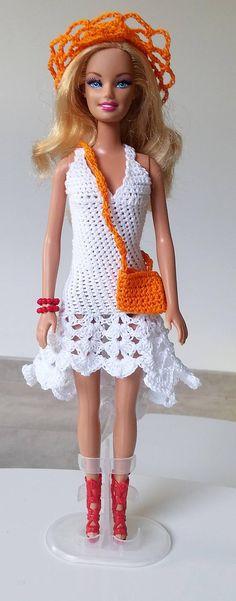 Robe blanche pour Barbie faite au crochet. Le lot comprend : 1 robe, 1 chapeau, 1 bracelet, 1 paire de chaussures et 1 sac à main. Vendu sans la poupée.